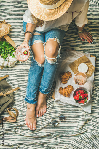 Keuken foto achterwand French style romantic picnic setting. Young woman in denim pants with glass of ice rose wine, strawberries, croissants, brie cheese, hat, sunglasses, peony flowers, top view. Outdoor gathering concept