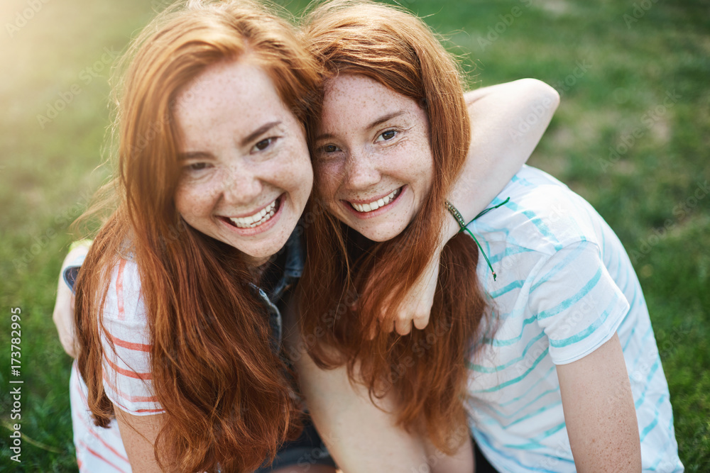 Fototapety, obrazy: Two identical sisters have so much in common. Hugging, smiling, spending time together outdoor on a sunny day. Twins are what boys dream of.