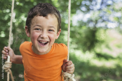 Cheerful boy swinging.