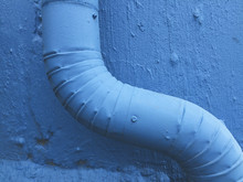 Close Up Of Painted Blue Gutter Pipe And Wall