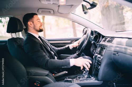 Zdjęcie XXL Przystojny biznesmen w siedzenie kierowcy w jego samochodzie i zmiany prędkości
