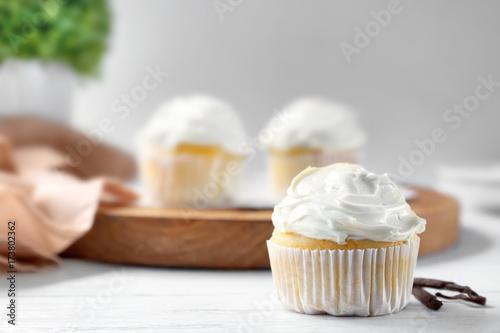 Tasty vanilla cupcake on wooden table Wallpaper Mural