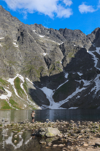 Lonely tourist taking pictures near the Black pond in High Tatra mountain in Poland Poster