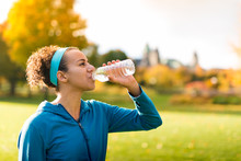 Young Woman Drinking From Water Bottle While Jogging In Ottawa In Autumn