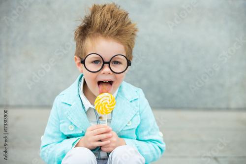 Pinturas sobre lienzo  Fashion kid with lollipop near gray wall