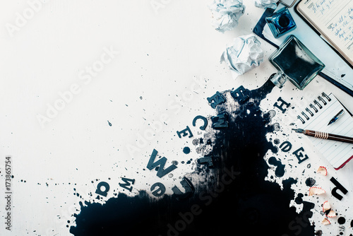 Foto  Header with spilled ink, crumpled paper, scattered letters, papers and notepads on a white wooden background