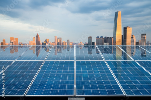 Fotografia  solar energy panel with city twilight