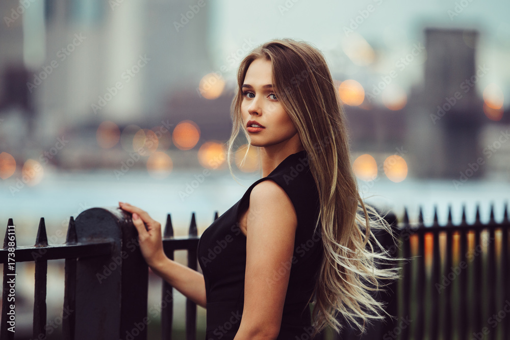 Fototapeta Gorgeous young model woman with perfect blonde hair looking at camera posing in the city wearing black evening dress.