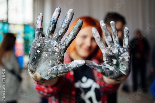 Fototapeta Young person showing hands covered with paint during mass art therapy session