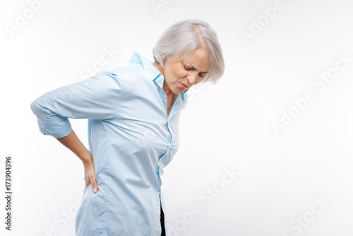 Carta da parati Grey-haired woman suffering from pain in lower back