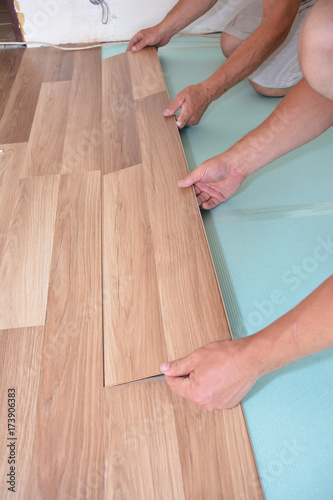 Contractors Installing Wooden Laminate Flooring With Insulation And