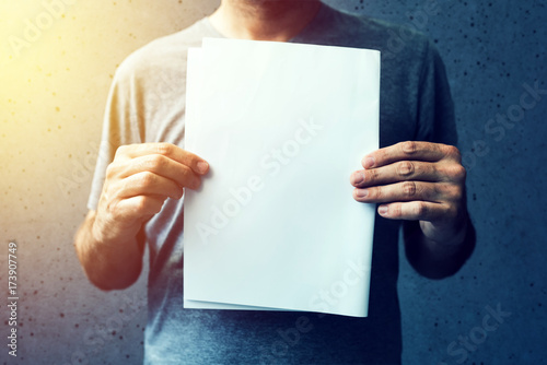 Fotografie, Obraz  Casual man holding blank A4 paper as copy space
