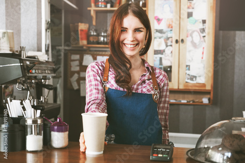 Fotografie, Obraz  Young female barista smiling, while serving a coffee at the counter