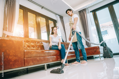 Fototapety, obrazy: Asian teen couple are helping to clean the house. Man pointing Man ordered to clean up the area in front of the sofa. Man shows discontent