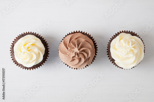 Photo  Cupcakes with whipped chocolate and vanila cream, on white wooden table