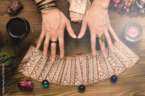 Photo  Fortune teller female hands and tarot cards on wooden table