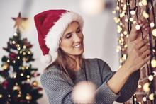 Woman Hanging Christmas Lights At Home.
