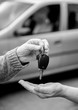 Woman giving car keys to another woman