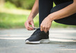 runner woman tie shoe in a park