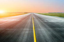 Asphalt Road With A Dividing Strip In The Horizon At Sunset.