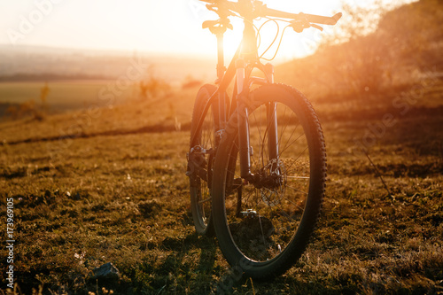 Fotobehang Fiets Mountain bike stands alone outdoor against autumn sunset landscape