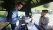Cheerful food vendor in burger van serving customers at summer festival