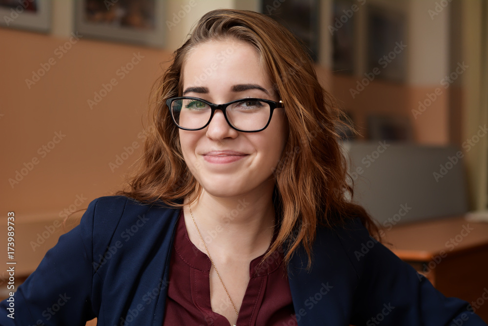 Fototapeta Close-up portrait of a young woman in glasses. A girl with red hair in the classroom. Business woman in training class