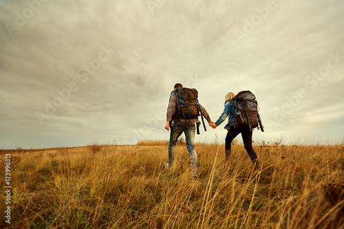 Plakat Młoda para podróżuje z plecakami na polu w naturze.