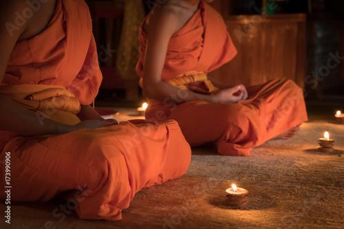 Obraz na plátně Novices monk vipassana meditation in front lighting candle