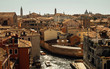 Aerial view of Venice with old rustic houses,boat canals and church towers across city.