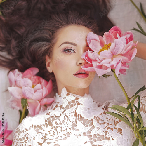 Fotografía  Beautiful young woman lies among peonies