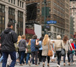 People walk across a busy Manhattan crosswalk in New York City during rush hour evening commute travel to work and home
