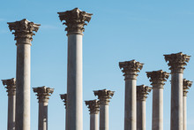 A Grouping Of Corinthian Columns Against A Clear Blue Sky.