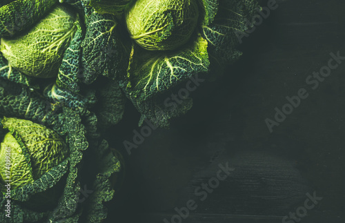 Foto Raw fresh uncooked green cabbage over dark background, top view, selective focus