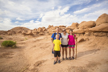 Cute Young Family On A Vacation Together. Hiking Among The Red Rock Formations Around Moab, Utah And Arches National Park.