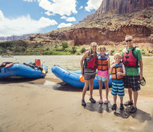 Smiling Young Family Ready To Board A Large Inflatable Raft As They Travel Down The Scenic Colorado River Near Moab, Utah And Arches National Park.