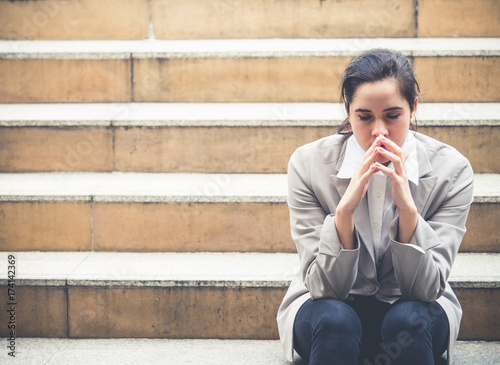 Upset young caucasian beautiful businesswoman tired from work sitting at stairs, Fototapeta