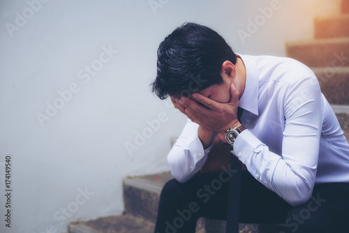 Portrait of a handsome young businessman who is sitting sadly disappointed by the business Fototapet