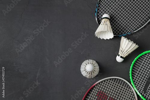 Shuttlecocks and badminton racket on black background. Wallpaper Mural
