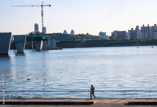 Fototapeta Osoba łowiąca w rzece w centrum miasta