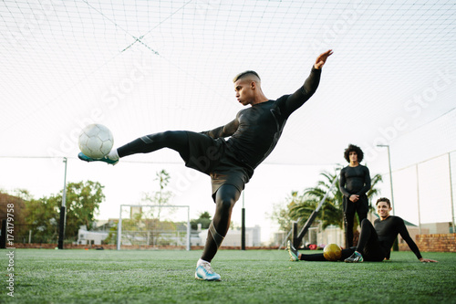 Player kicking soccer ball on field