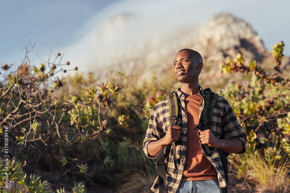 Fototapety, obrazy: Smiling young African man out for a mountain hike