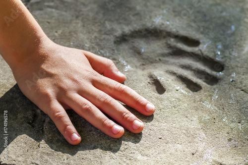 Fotografie, Obraz  Childs hand and memorable handprint in concrete