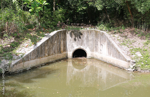 Valokuvatapetti The concrete circular run-off pipe discharging water.