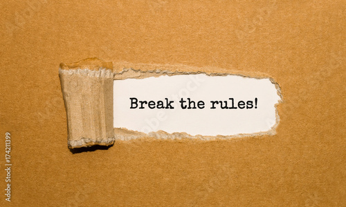 Fotomural The text Break the rules appearing behind torn brown paper