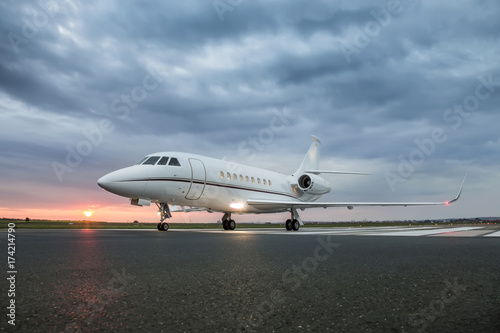 Valokuvatapetti Modern advanced private business jet ready to take off with sunrise in the backg