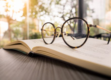 Reading Books Concept, A Glasses On Old Book On Wooden Desk In The Morning With Sunlight