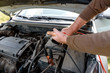 Car mechanic using battery jumper cables to charge dead battery. Charging car battery with electricity trough jumper cables with copper clamps, copy space. Recharging battery on the road