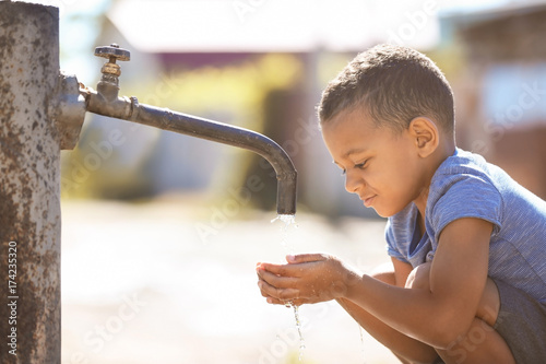 Fotografía  African American child drinking water from tap outdoors