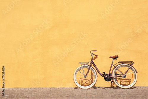 Stylish new bicycle near color wall outdoors